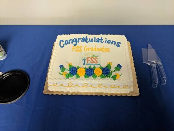A cake sitting on a blue table with the words Congratulations FSS Graduates done in icing on the cake.
